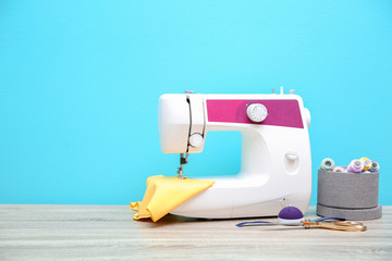 Sewing machine on table against color background