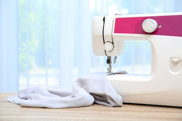 Sewing machine on table near window indoors
