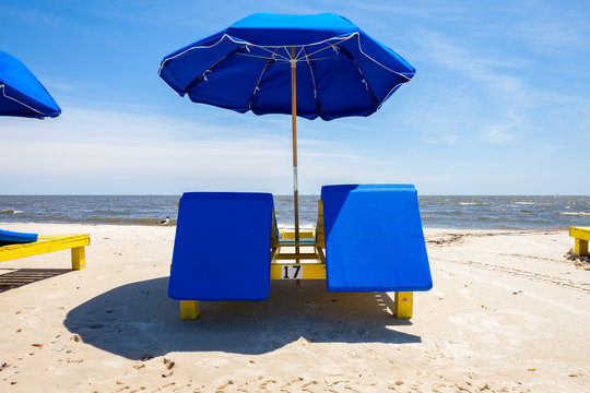 Gulf coast beach in Biloxi, Mississippi with lounge chairs along the shoreline.