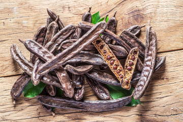 Carob pods and carob beans on the wooden table.