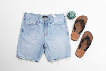 Flat lay composition with jean shorts and slippers on white background Fototapete