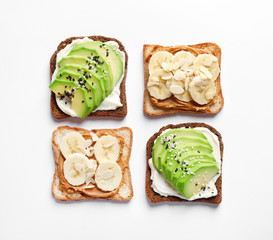 Tasty toast bread with banana and avocado slices on white background