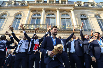 France's goalkeeper Hugo Lloris holds the winner's trophy in front of his team mates during an official reception at the Elysee Presidential Palace in Paris