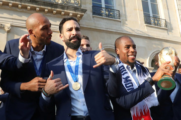 France's defender Djibril Sidibe holds the winner's trophy as France's midfielder Steven N'Zonzi  speaks with defender Adil Rami during an official reception at the Elysee Presidential Palace in Paris