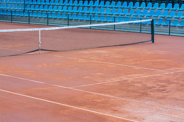 empty clay tennis court and net in time-out