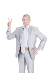 Mature businessman showing victory sign .isolated on white