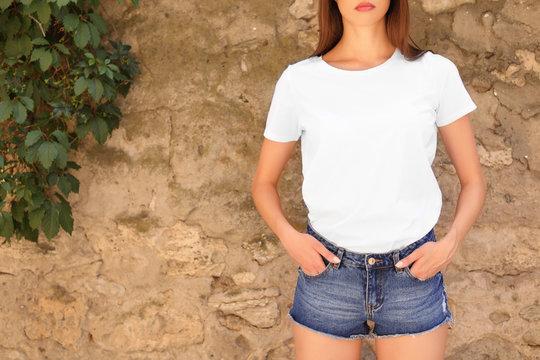 Young woman wearing white t-shirt near stone wall on street