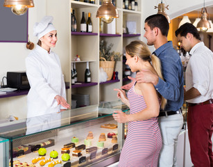 Cheerful pastry chef woman is offering cakes from showcase