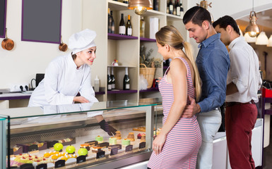 Young chef female is serving visitors