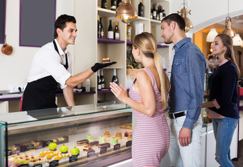 Man seller serving visitors in cozy pastry store