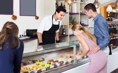 Positive man confectioner serving visitors