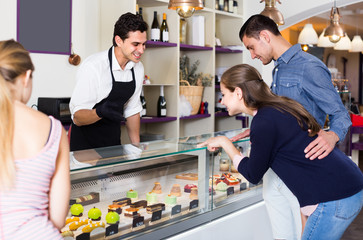 Couple with woman friend are choosing delicious cakes from showcase