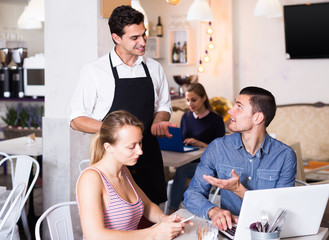 Portrait of attentive cafe waiter standing at table and talking to guests