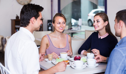 group of four friends enjoying coffee at pastry bar