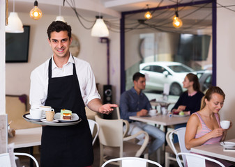 Portrait of young waiter inviting to coffee
