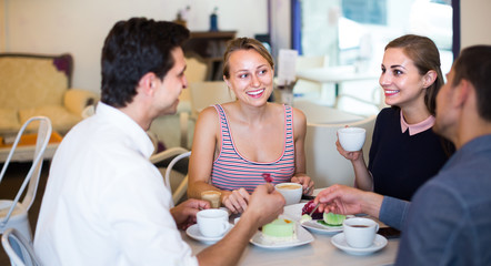 group of four happy friends enjoying coffee at pastry bar