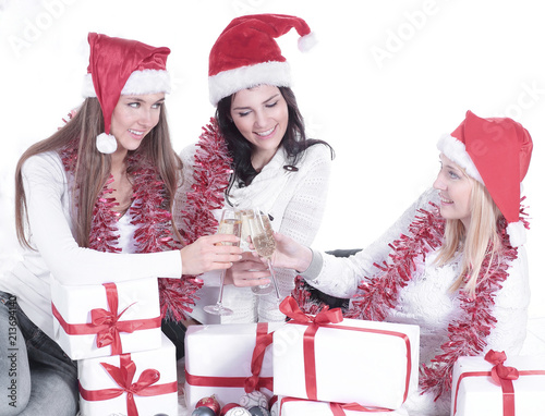 three young women in hats of Santa Claus with Christmas gifts a ...