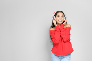 Young woman listening to Christmas music on color background
