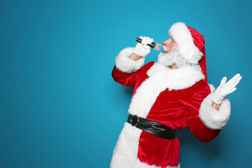 Santa Claus singing into microphone on color background. Christmas music