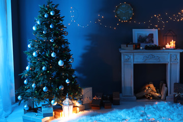 Stylish living room interior with Christmas tree and fireplace at night