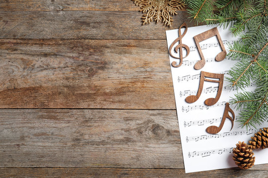 Composition with music sheet and notes on wooden background. Christmas songs concept
