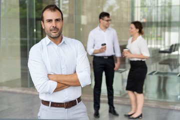 Portrait of confident mid adult leader standing with folded arms. Caucasian businessman looking at camera outdoors, his colleagues talking in background. Business leader concept
