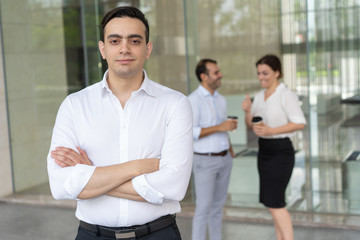 Portrait of serious young Caucasian businessman standing with folded arms. Confident entrepreneur standing and looking at camera, his colleagues talking in background. Leadership concept
