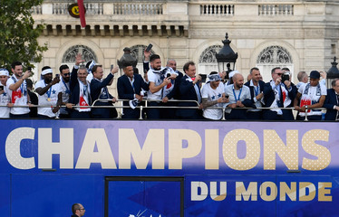 France's national soccer team players take pictures with their mobile phones as they celebrate with teammates on the roof of a bus while parading down the Champs-Elysee avenue in Paris