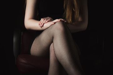 Girl in black fishnet stockings against dark background. Sexy woman in stockings sitting on chair. Strict woman domination bdsm concept.