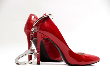 Handcuffs and sexy red high heels on white background. Fetish erotic bsdm concept. Strict woman domination concept. Corporal punishment