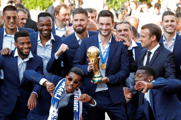 French President Emmanuel Macron poses with France soccer team captain Hugo Lloris holding the trophy, and players before a reception to honour the France soccer team at the Elysee Palace in Paris