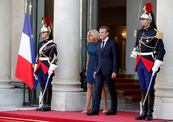 French President Emmanuel Macron and his wife Brigitte Macron wait for France players to arrive to attend a reception to honour the France soccer team after their victory in the 2018 Russia Soccer World Cup, at the Elysee Palace in Paris