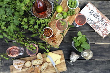 Overhead view of food with wine and plants on wooden table