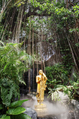 Golden Buddha statue against aerial roots in forest at Wat Saket