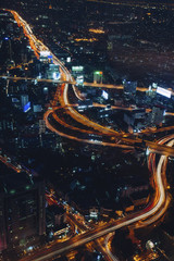 Aerial view of light trails on road amidst city at night