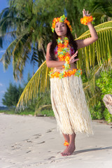 Hula Hawaii dancer dancing on the beach with palms trees. Ethnic woman in costume dancer Hawaii hula dancing in a tropical nature.