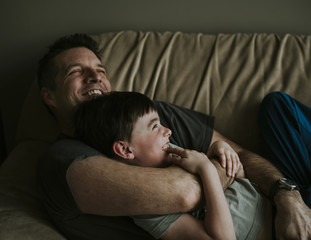 Happy father embracing son while lying on sofa at home