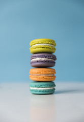 Close-up of colorful macaroons on table against blue background