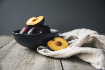 Close up of plums in bowl with napkin on wooden table against gray background