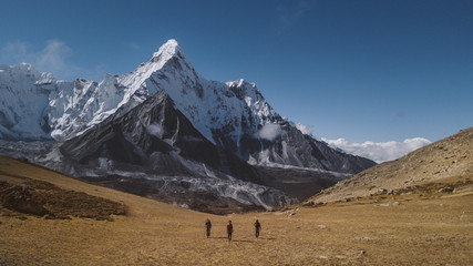 Rear view of hikers walking on landscape against blue sky at Sagarmatha National Park