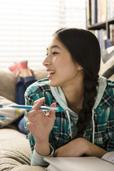 Smiling teenage girl looking away while doing homework on couch at home