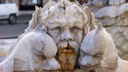 Marble mask with animals of a fountain in Piazza Navona in Rome in a sunny day