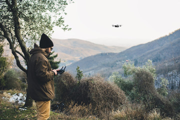 Side view of male hiker flying quadcopter while standing on mountain against clear sky