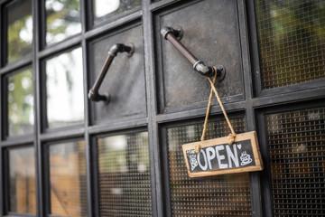 Open coffee shop sign on door