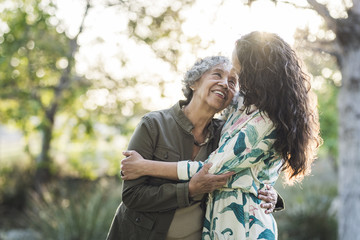 Happy mother and daughter embracing while standing at park
