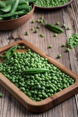 Fresh organic green peas on rustic wooden table, harvest time