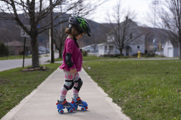 Side view of girl roller skating on footpath at park