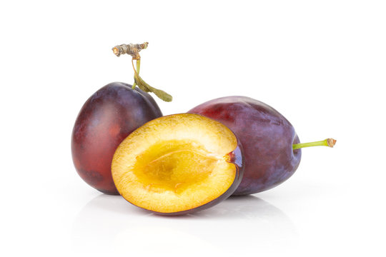 Group of two whole one half of fresh violet-blue plum vibrant moyer variety isolated on white