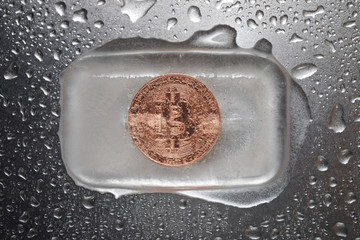 Overhead view of bitcoin in ice on wet metallic table
