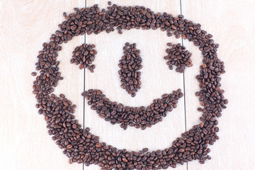 funny face of black coffee beans on wooden background